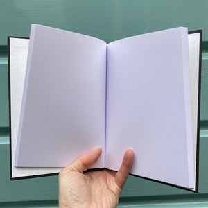 Hardback journal held open in a hand showing plain white pages within