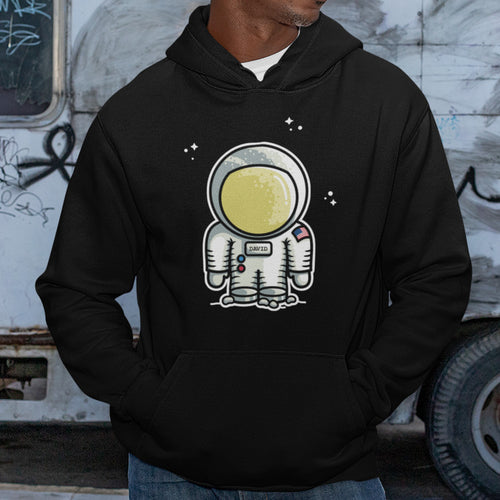The torso of a black man wearing a black hoodie with his hands in the hoodie front pouch and the design of a cute astronaut and stars on his chest personalised with the name David