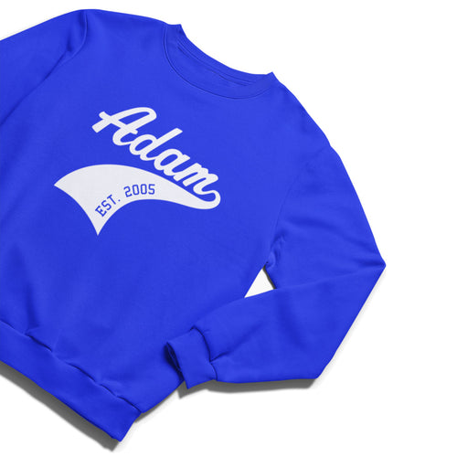 A bright royal blue crewneck sweatshirt laid flat with the name Adam in a thick italic white font with a tail coming from the end of the word swishing down and with EST. 2005 punched through the swish