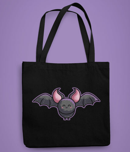 A black tote bag laid flat on a purple background with a design in the center of a cute grey and pink bat