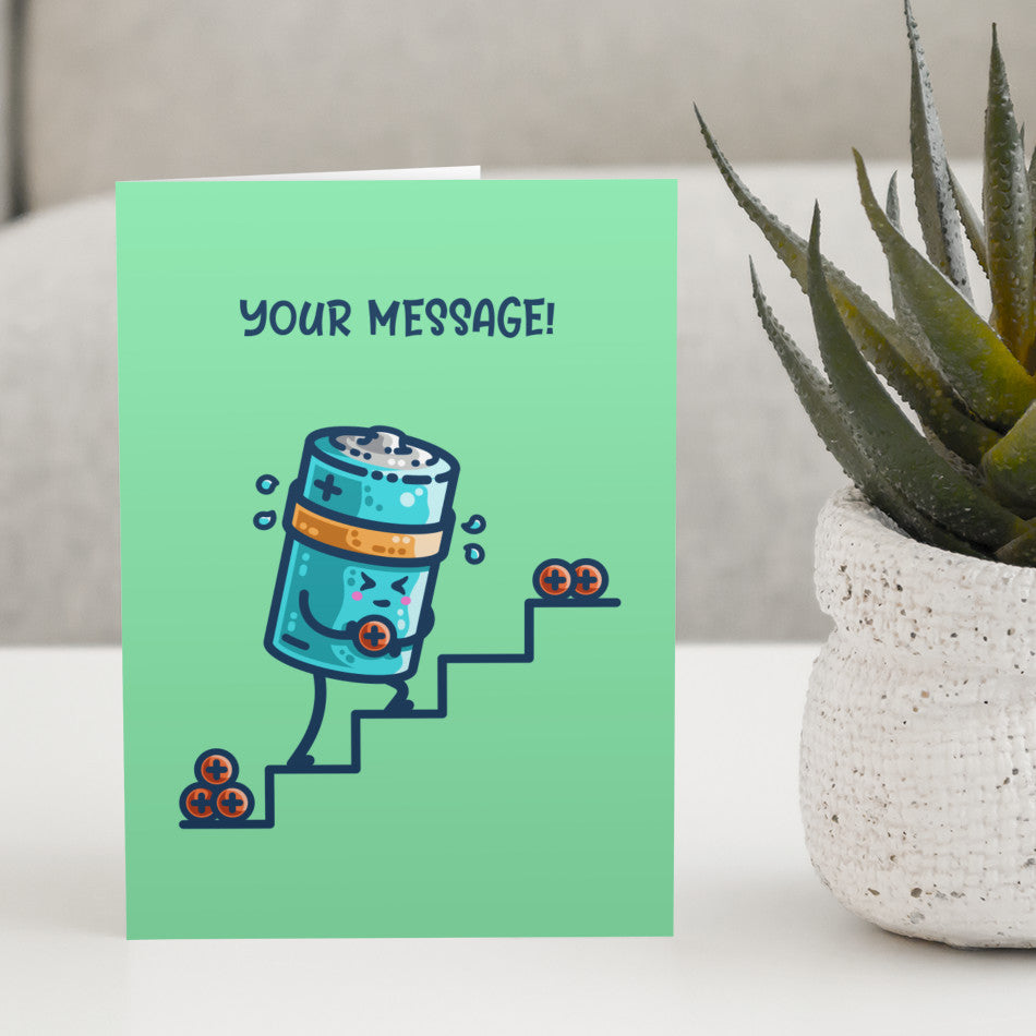 A green greeting card standing on a white table next to a plant, the card has a design of a kawaii cute cylindrical blue battery working hard, sweating, carrying a positive charge up some steps and the words your message written above