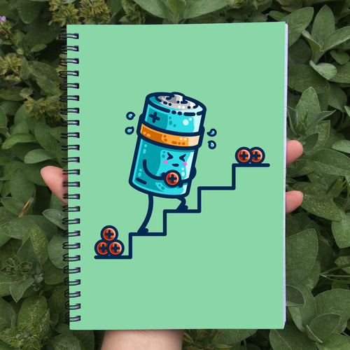Held in a hand is a closed spiral notebook showing a pale green front cover with a design of a kawaii cute cylindrical blue battery working hard, sweating, carrying a positive charge up some steps.