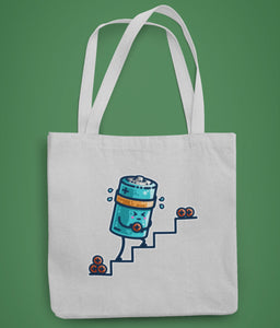 A pale grey coloured fabric tote bag lying flat against a green background with a design in the center of a kawaii cute cylindrical blue battery working hard, sweating, carrying a positive charge up some steps.
