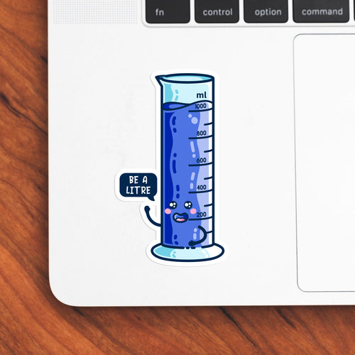 The bottom left hand corner of a laptop computer keyboard with a vinyl sticker stuck to it. The blue sticker is the shape of a graduated cylinder with smily face with a speech bubble saying be a litre.