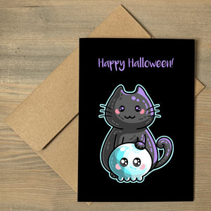 A brown envelope beneath a black greeting card that features a kawaii cute black cat with its paw on a blue skull with a personalised message above.