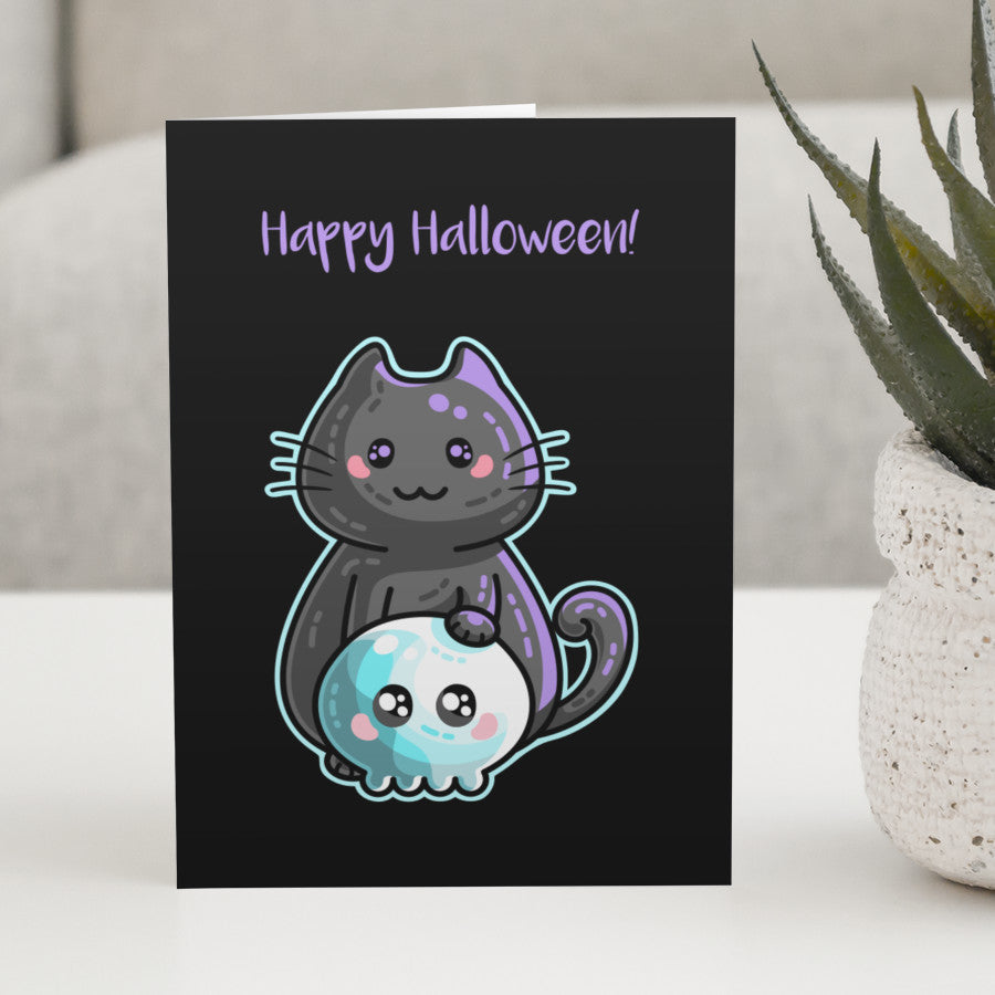 A black greeting card standing on a white table with a design of a kawaii cute black cat with its paw on a blue skull with a personalised message above.