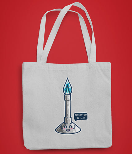 A pale grey coloured fabric tote bag lying flat against a red background with a design in the center of a cute bunsen burner with a blue flame and a speech bubble saying chemistry is lit!