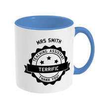 Load image into Gallery viewer, Personalised black circular banner design with the words 'terrific teaching assistant' on a two toned blue and white ceramic mug, showing RHS