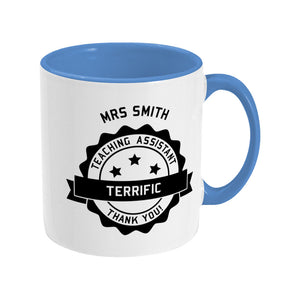 Personalised black circular banner design with the words 'terrific teaching assistant' on a two toned blue and white ceramic mug, showing RHS