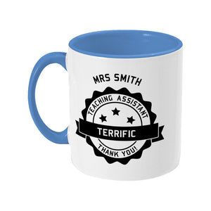 Personalised black circular banner design with the words 'terrific teaching assistant' on a two toned blue and white ceramic mug, showing LHS