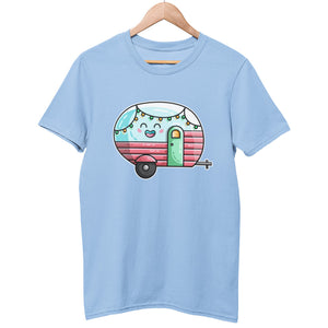 A pale sky blue unisex crewneck t-shirt on a hanger with a design on its chest of a kawaii cute blue vintage style caravan seen side on with the tow bar to the right and with a green door and pink panelling on the bottom half of the caravan and a string of coloured lights looping across the top