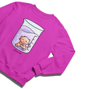 A bright pink unisex crewneck sweatshirt laid flat with a design on its chest of a ginger cat sitting in a glass chemistry beaker of purple liquid, joining atoms into molecules, with the word catalyst in black capital letters beneath