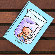Load image into Gallery viewer, Blue notebook with black spiral binding lying on wooden slats, notebook design is of a cute ginger cat in a chemistry beaker and the word catalyst