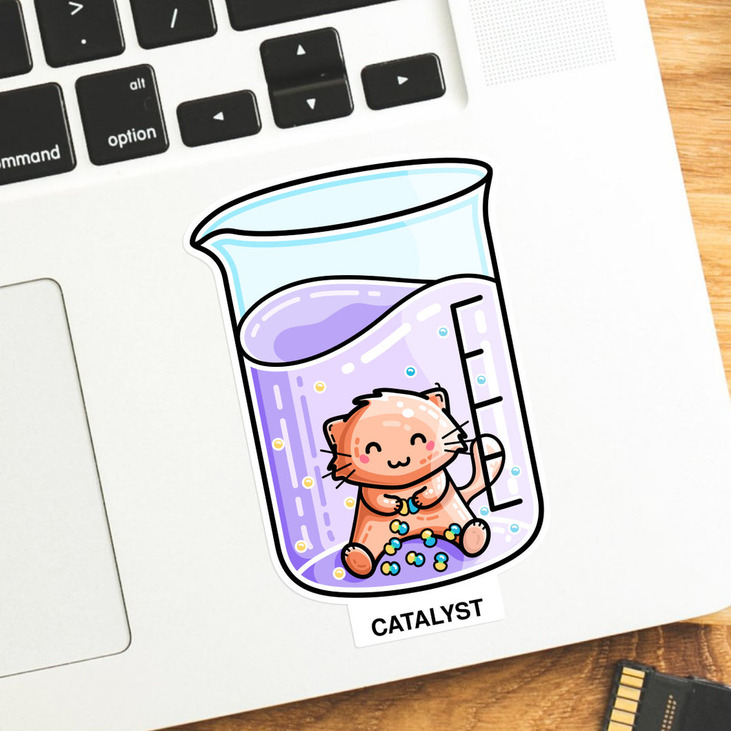 Vinyl sticker of a cute cat in a chemistry beaker joining atoms with the word catalyst, the sticker is on a laptop computer keyboard