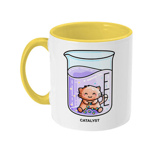 A two toned yellow and white ceramic mug, handle to the left, featuring a design of a cute cat joining atoms in a chemistry beaker of liquid and the word catalyst beneath.