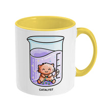 Load image into Gallery viewer, A two toned yellow and white ceramic mug, handle to the right, featuring a design of a cute cat joining atoms in a chemistry beaker of liquid and the word catalyst beneath.