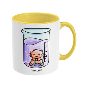 A two toned yellow and white ceramic mug, handle to the right, featuring a design of a cute cat joining atoms in a chemistry beaker of liquid and the word catalyst beneath.