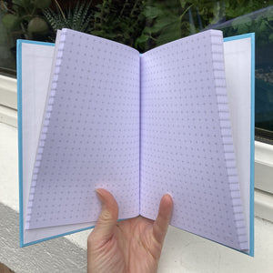 Hardback journal held open in a hand showing grid graph paper within