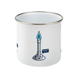 A silver rimmed white enamel mug showing a side view with the handle hidden from view behind it and a design of a cute Bunsen burner with blue flame and speech bubble saying chemistry is lit!