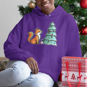 A black woman sitting next to a Christmas tree wearing a purple hoodie with the neck cords tucked in and with the design of a cute fox sitting looking up at a Christmas tree with a wrapped gift beneath it