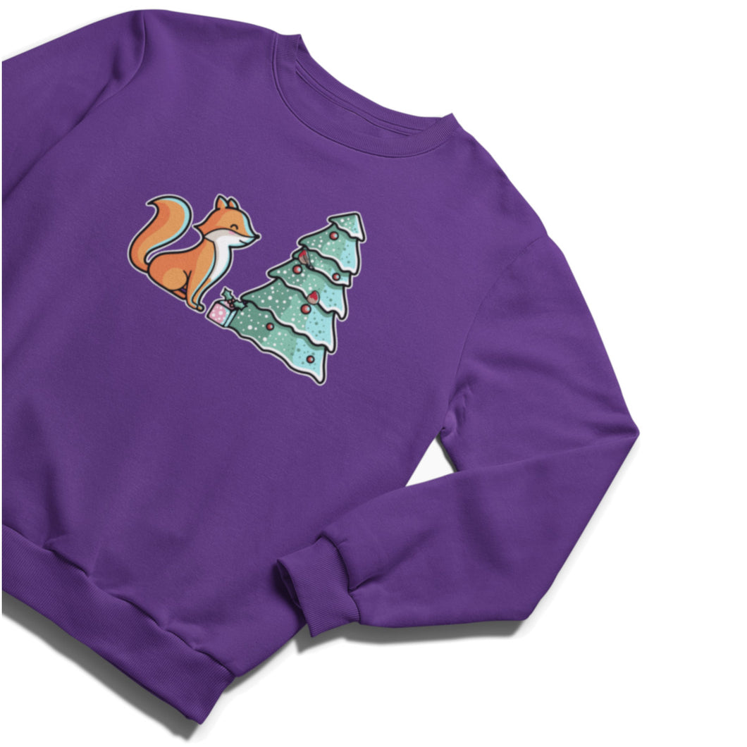 A purple unisex crewneck sweatshirt laid flat at an angle with a design of a cute red fox sitting sideways on looking at a decorated Christmas tree and with a present at its feet.