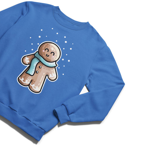 A blue unisex crewneck sweatshirt laid flat at an angle with a design of a kawaii cute gingerbread person wearing a blue scarf and with dots of white snow falling from above
