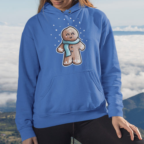 Torso of a woman wearing a royal blue coloured hoodie with the neck cords tucked away and a design on the chest of a gingerbread person wearing a blue scarf with dots of snow falling around