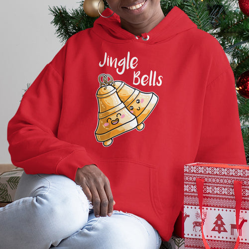 Torso of a woman sitting on the floor beneath a Christmas tree wearing a red hoodie with the neck cords tucked away and a design on the chest of two kawaii cute happy ringing bells with the white text Jingle Bells written above