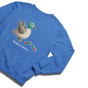 A blue unisex crewneck sweatshirt laid flat at an angle with a design of a kawaii cute mallard duck with its wings raised in alarm and a newly pulled open Christmas cracker at its feet, and the words Christmas Quacker written beneath.