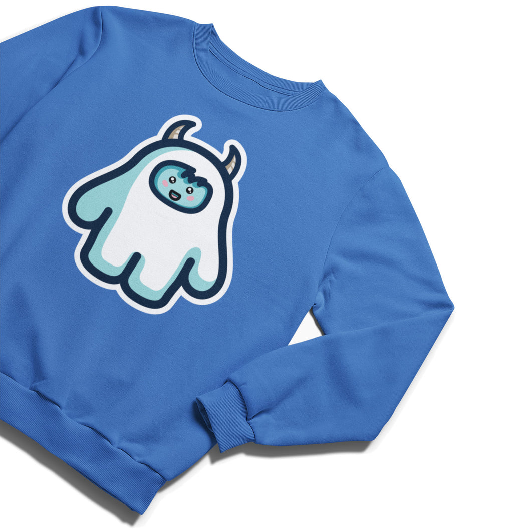 A blue unisex crewneck sweatshirt laid flat at an angle with a design of a white yeti figure with horns on its head and a cute smiling face
