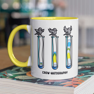 A two toned white and yellow ceramic mug with the handle to the left, standing on a thick book, showing a design of 3 crows holding strips of paper into 3 test tubes showing colour separation.