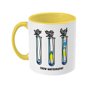 A two toned white and yellow ceramic mug with the handle to the left showing a design of 3 crows holding strips of paper into 3 test tubes showing colour separation.