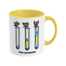 Load image into Gallery viewer, A two toned white and yellow ceramic mug with the handle to the right showing a design of 3 crows holding strips of paper into 3 test tubes showing colour separation.