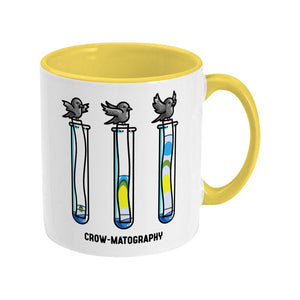 A two toned white and yellow ceramic mug with the handle to the right showing a design of 3 crows holding strips of paper into 3 test tubes showing colour separation.