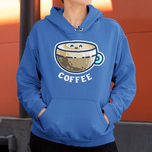 Torso of a woman wearing a blue unisex hoodie with her hands in the front pouch and the cords tucked in with a design on the chest of a kawaii cute glass cup of coffee with a thick creamy layer at the top and a smiling face in the cream on the top. The word coffee is in white capital letters beneath.