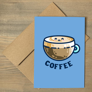 A blue greeting card lying flat on top of a brown envelope. In the center of the card is a design of a kawaii cute glass cup of coffee with a thick creamy layer at the top and a smiling face in the cream on the top. The word coffee is in capital letters beneath.