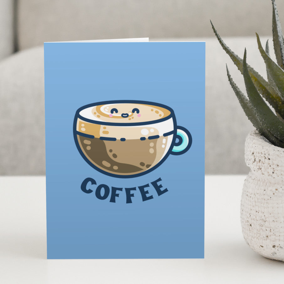 A blue greeting card standing on a white table next to a plant and with a design on the card of a kawaii cute glass cup of coffee with a thick creamy layer at the top and a smiling face in the cream on the top. The word coffee is in capital letters beneath.