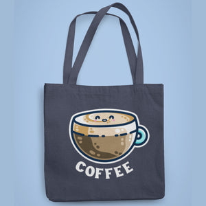 A dark blue coloured fabric tote bag lying flat against a pale blue background with a design in the center of a kawaii cute glass cup of coffee with a thick creamy layer at the top and a smiling face in the cream on the top. The word coffee is in white capital letters in an arc beneath.