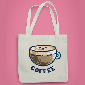 A natural coloured fabric tote bag lying flat against a pink background with a design in the center of a kawaii cute glass cup of coffee with a thick creamy layer at the top and a smiling face in the cream on the top. The word coffee is in dark blue capital letters in an arc beneath.