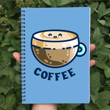 Load image into Gallery viewer, Closed spiral notebook with a blue cover featuring a design of a kawaii cute glass cup of creamy latte with the word coffee beneath in dark blue capital letters