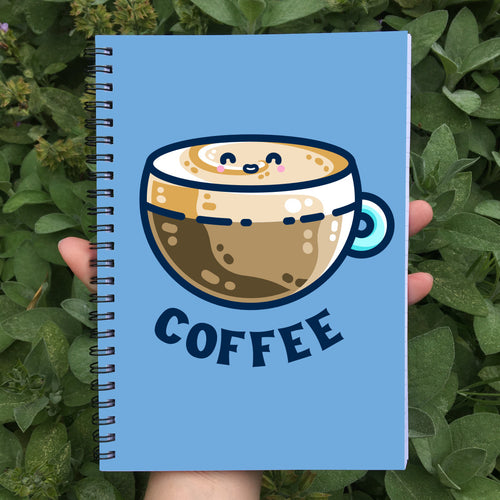 Closed spiral notebook with a blue cover featuring a design of a kawaii cute glass cup of creamy latte with the word coffee beneath in dark blue capital letters