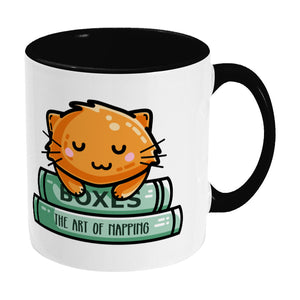 Cute ginger cat asleep on books design on a two toned black and white ceramic mug, showing RHS