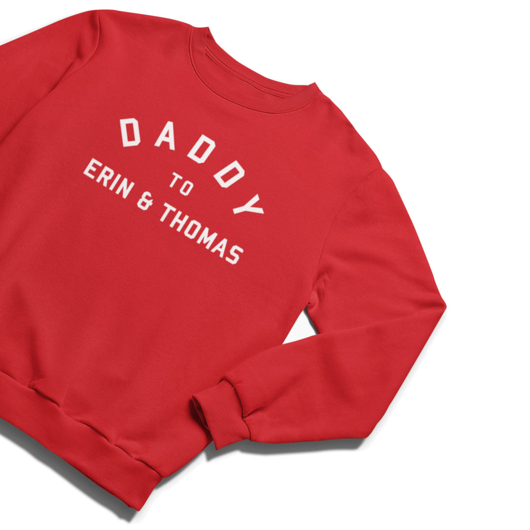 Photo of a red sweatshirt with the words Daddy To Erin & Thomas printed onto the chest in white college style capital letters text