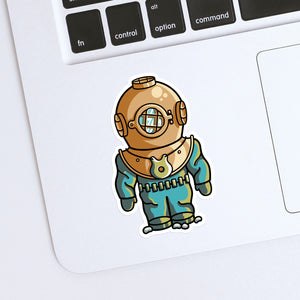 A shaped vinyl sticker of an old fashioned style diving suit with bronze coloured helmet shown stuck onto the bottom left hand corner of a laptop computer keyboard
