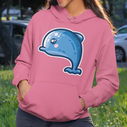 The torso of a woman wearing a candyfloss pink hoodie with her hands in the front pouch and the neck cords tucked in with a design on the chest of a kawaii cute blue dolphin