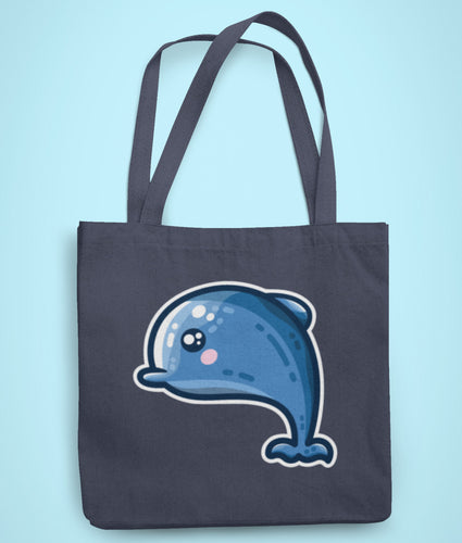 A dark blue coloured fabric tote bag lying flat against a pale blue background with a design in the center of a kawaii cute blue dolphin facing to the left with a white border around it.