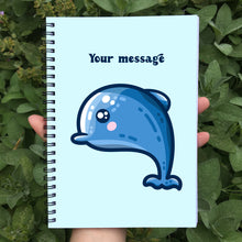Load image into Gallery viewer, Closed notebook showing the blue front cover with personalised message and cute dolphin design