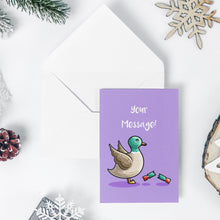 Load image into Gallery viewer, An open white envelope beneath a green greeting card with a design of a cute mallard duck with wings up in alarm at a pulled red and green Christmas cracker at its feet and the words Christmas quacker in white above
