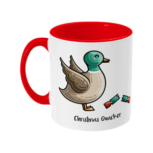 A two toned white and red ceramic mug with the handle to the left showing a design of a mallard duck with a red and green Christmas cracker and the words Christmas Quacker written in black beneath