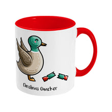 Load image into Gallery viewer, A two toned white and red ceramic mug with the handle to the right showing a design of a mallard duck with a red and green Christmas cracker and the words Christmas Quacker written in black beneath